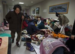 Japanese people fill an evacuation center trying to keep warm as winter weather made a miserable situation worse on March 17, 2011 in Minamisanriku, Japan.