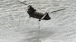 A military helicopter scoops water off Japan's northeast coast on its way to Fukushima Dai-ichi nuclear power plant on Thursday, in an effort to cool overheated fuel rods inside the core.