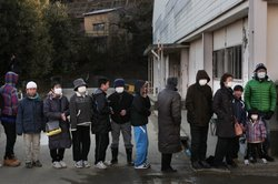 People line up to collect noodles and soup at an evacuation center on March 17, 2011 in Kensennuma, Japan. Residents were allowed back to their homes today and began the massive clean-up operation caused by a 9.0 magnitude strong earthquake that struck on March 11 off the coast of north-eastern Japan.