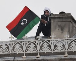 An anti-Gaddafi protestor sits on the roof of the Libyan Embassy on March 17, 2011 in London, England. Police are surrounding the embassy after protestors climbed onto the roof yesterday.