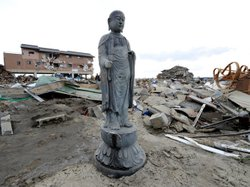 A religious statue stands amid the debris left by last Friday's tsunami in Na...