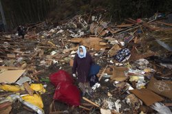 Kiyoko Kin searches through the rubble of part of her house that was washed a...