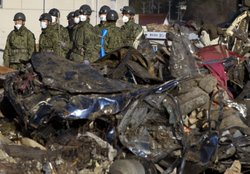 Japanese military search a collapsed building for bodies March 27, 2011 in Kensennuma, Japan.
