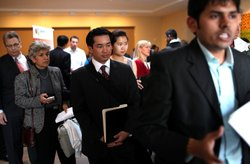 Job seekers wait in line to speak with a job recruiter at the Green Jobs and ...