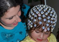 Avalyn Montani, whose older brother has autism, is participating in an infant/sibling study at Children's Hospital Boston. She is wearing an elastic band covered with sensors on her head.