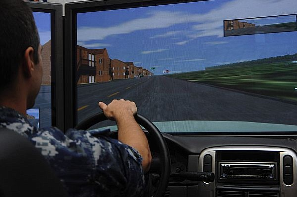 Intelligence Specialist Seaman Cory Bottie drives a simulator during the Save...
