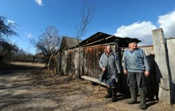 Ivan Semenyuk, 75, and his wife Maria,73, stand outside their house in the la...