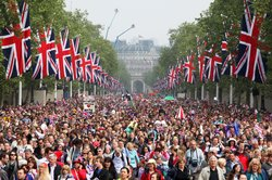 Well wishers with flags surge along the Mall towards Buckingham Palace to cel...