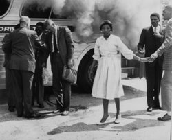 Freedom Rider Mae Frances Moultrie Howard stands outside the burning Greyhound bus in Anniston, Alabama on May 14, 1961.