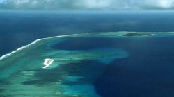 Bikini Atoll. The large circular area of dark blue water is the crater left b...