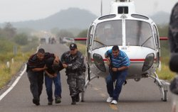 Mexican police escort a suspected drug trafficker off a helicopter in Hermosillo, Mexico.
