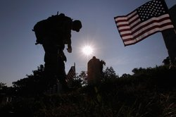 Members of the 3rd U.S. Infantry Regiment place American flags at the graves ...