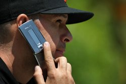 Sal Mora talks on his cellular phone as he sits in a park in San Francisco, C...