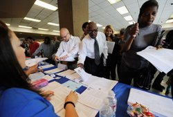 Job seekerJeffery Sizemore (C) picks up fliers from potential employers during the Los Angeles Mission's 10th annual Skid Row Career Fair June 2, 2011 in Los Angeles, California.