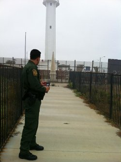 A Border Patrol agent stands in front of the historic marker between Tijuana ...