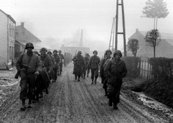 U.S. troops of the 28th Infantry Division, who have been regrouped in security platoons for defense of Bastogne, Belgium, march down a street. Some of these soldiers lost their weapons during the German advance in this area. Bastogne, Belgium, December 20, 2944.