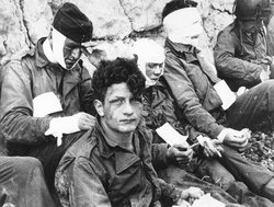 "Normandy Invasion, June 1944. Wounded men of the 3rd Battalion, 16th Infantry Regiment, 1st Infantry Division, receive cigarettes and food after they had stormed ""Omaha"" beach on D-Day, June 6, 1944."