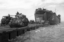"Normandy Invasion, June 1944. Coast Guard manned USS LST-21 unloads British Army tanks and trucks onto a ""Rhino"" barge during the early hours of the invasion, June 6, 1944. Note the nickname ""Virgin"" on the ""Sherman"" tank at left."