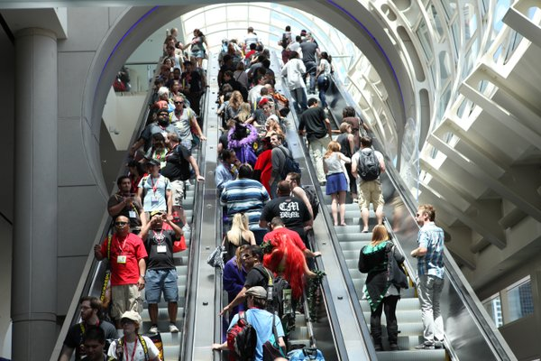Crowds on Day One of Comic-Con International taking the escalator to the upper level of the convention hall where many of the panels take place.