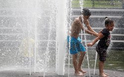 Anthony (L) and Yarelis Martinez play in the fountain in Manhattan's Washington Square Park July 21, 2011 in New York City.