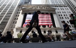 People walk past the New York Stock Exchange during afternoon trading on August 4, 2011 in New York City.