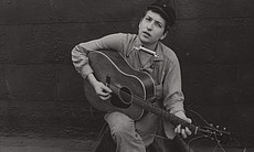 "Promotional photo of young Bob Dylan with guitar. Dylan performs ""Blowin' in the Wind"" in ""Legends Of Folk: The Village Scene."""
