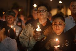 Mourners gather for a candlelight vigil in City Heights on Friday, August 11,...