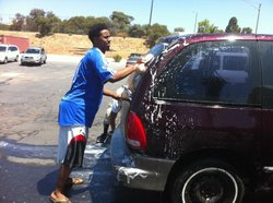 A member of the Somali Youth League participates in a car wash fundraiser in ...
