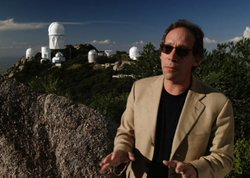 "Lawrence Krauss, Ph.D., professor of earth and space exploration at Arizona State University, explains ""dark energy"" in the program. Behind him is the Kitt Peak National Observatory (KPNO), located above the Sonoran Desert on the Tohono O'Odham Reservation near Tuscon, Arizona."