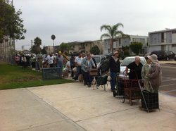 People wait in line to receive emergency food aid from the San Diego Food Ban...
