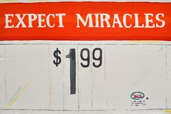 "Jean Lowe's ""Expect Miracles"" price sign hung above supermarket-inspired works at ""Discount Barn"" (Enamel on cardboard, wood, 2011)."