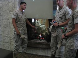 """Marines at """"The Hearth,"""" a two way fire place in the communal area of the new barracks building."""