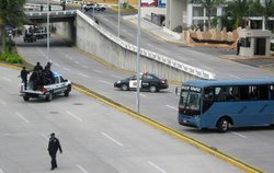 Mexican authorities guard the site where 35 bodies were found beneath an overpass Tuesday in Boca del Rio in Veracruz State.