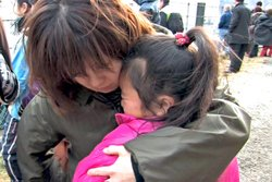 Refugees comfort one another after the earthquake and tsunami that hit the northern coast of Japan on March 11, 2011.