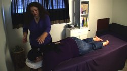 Malou Gibson gives a massage to a client at her store