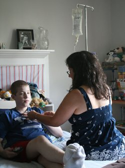 Laura Zakhar connects her son, Kevin, 15, to the