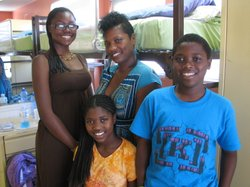 """Monique Blackmon and her three children, Deja (aged 16), Trinity (11) and Zion(12) in their room at the intake center of """"Solutions for Change,"""""""