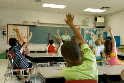 Young students raise their hands in a classroom.