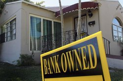 A bank-owned sign is seen in front of a foreclosed home in Miami. Florida was...