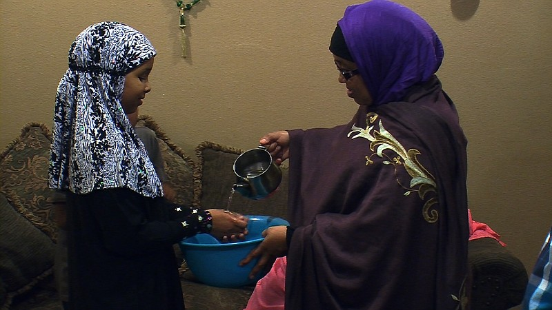 Somali refugee Mana Ahmed Mohamed helps her daughter Idil Nunow wash her hand...