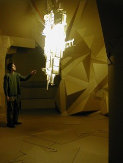 Jason Rogenes stands by one of his sculptures made out of expanded polystyrene, electrical components, and eight fluorescent lamps.