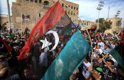 Libyans wave their new national flag as they celebrate in the streets of Trip...