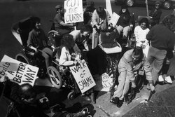 Protesters break a curb, likely in the late 1960s.