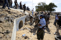 Libyan National Transitional Council (NTC) fighters gather outside large concrete pipes where ousted Libyan leader Moamer Kadhafi was allegedly captured in the coastal Libyan city of Sirte on October 20, 2011.