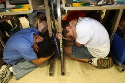 Students of Stevenson Elementary School in Los Angeles drop, cover and hold on during the simulation of an expected catastrophic 7.8 magnitude earthquake on the San Andreas Fault during the Great Southern California ShakeOut earthquake drill.