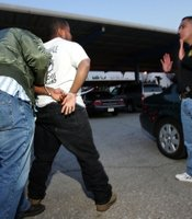 A man is searched before being booked after his arrest by a female police officer who arrested him while posing as a prostitute on Holt Boulevard, known to sex workers throughout southern California as 'the track', during a major prostitution sting operation November 12, 2004 in Pomona, California.