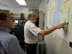 Cybersecurity analysts look at a diagram that shows their computer network, w...
