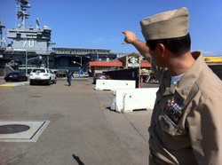 Dave Nagle, Senior Chief Petty Officer, U.S. Navy, points to the stands being built on the deck of the USS Carl Vinson.