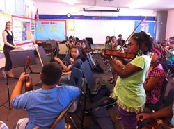 Laura Smith, a music teacher for San Diego Unified, watches as Raynisha Fields, 9, performs a solo in her fourth grade orchestra class at Zamorano Elementary School, Oct. 17. 2011.