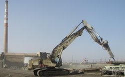 A 62-ton excavator hammers into a concrete foundation at the former ASARCO site.